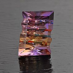 "Ametrine ""GEM-INTRUSION"" technique consists of precisely inserting solid colored gemstones into a faceted and carved transparent host gem. The result is a play of colors like a visual kaleidoscope, a gem with internal ""fireworks""."