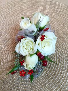 Corsage with white spray roses, red hypericum berries, red gems, and silver ribbon.