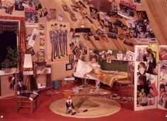 Tienerkamer, meisje in bed en de wanden en plafond beplakt met foto's en posters van de Beatles en andere popsterren van de jaren '60.