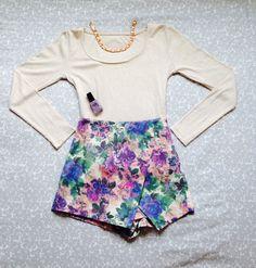 Floral skort, long sleeve plain top, pink choker and lilac gel nail varnish.