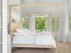 Peaceful white cottage bedroom boasts a blond carved wood canopy bed dressed in white hotel bedding and positioned against a white shiplap wall. All White Bedroom, White Rooms, Master Bedroom, Airy Bedroom, White Bedding, Live Edge Furniture, Bedroom Furniture, White Furniture, Wood Canopy Bed