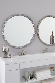 The Howard Elliott Memphis Mirror, shown here in a bathroom setting, is a striking piece featuring a round frame characterized by a wrinkled ripple texture. The texture and movement of the piece is exaggerated by its bright nickel plating applied with an electrostatic technique. It is a perfect focal point for an entryway, bathroom, bedroom or any room in your home.   #bathroommirror #roundmirror #modernmirror #howardelliottmirror