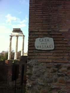 House of the Vestal Virgins in the Roman Forum sign - with three remaining CORINTHIAN columns of the Temple of Castor and Pollux in the background