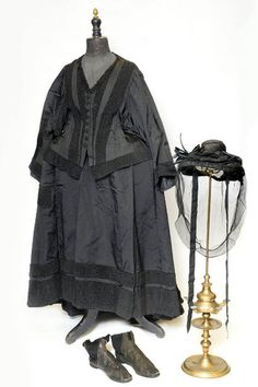 "Queen Victoria: The 1880s black ensemble consisted of a silk taffeta and bomberdine bodice, coupled with a matching 43 inch waist grosgrain skirt.  There was also a black straw hat with mourning veil, mounted with an ostrich feather, while a pair of silk bloomers and a chemise also featured, both monogrammed with VR for ""Victoria Regina"".  Rounding off the look was a pair of circa 1885 leather boots with elasticated sides."
