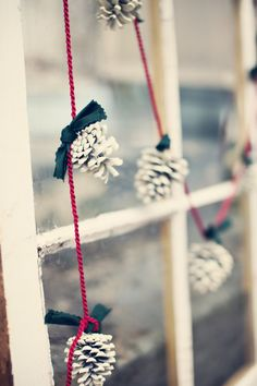 white pine cone garland for Christmas decor - DIY by spray painting pine cones white, adding green ribbon, and tying to a red string