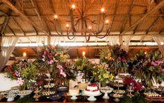 Mesa de doces colorida com três bolos em alturas e estilos diferentes. Foto: Mel e Cleber