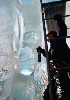 Junichi Nakamura uses a very small torch to work on a very large ice sculpture  (24 feet tall!) From the World Ice Art Championships in Fairbanks, Alaska