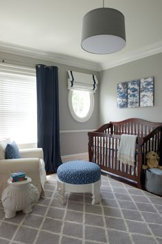 Gray and blue nursery features a gray drum pendant, Land of Nod Hangin' Around Ceiling Lamp, illuminating an ivory slipcovered glider with rolled arms adorned with a blue geometric pillow paired with a Serena & Lily Ellie Side Table and a White Chakki Stool atop a gray lattice rug placed in front of windows dressed in navy grommet curtains next to oval window covered in a navy grosgrain roman shade.