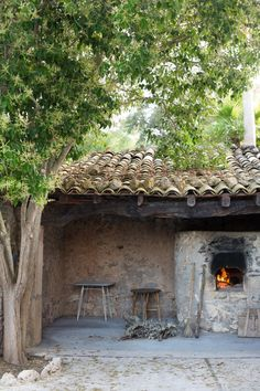A wood-burning outdoor fireplace is adjacent to a shaded dining patio.