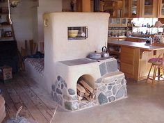 A beautiful cob wood stove using the cob thermal mass to heat a bed behind the cooking area in front.  Different sections provide more or less heat for cooking and warming, with slate flagstones for the cookplates.  With a rocket stove, the woodgas burns in the upright chamber; no smoke or creosote to clean out of the chimney running under the bed.  An external steam vent allows the moisture and CO2 (the exhaust) to dissipate harmlessly outside.