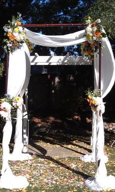 Iron Chuppah, draped in white with colorful flower arrangements bunched at the corners. Flowers include mums, lilies, dahlias, seeded eucalyptus.  Petal Town Flowers #winecountryweddingflowers #Sonomacountyweddingflowers #petalumaflorist #chuppahflowers