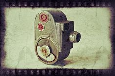 """""""Vintage 1950's Movie Camera"""" is a great center piece for a rustic farmhouse. The antique feel exudes from this photo. The camera is a 1950'S Bell and Howell 8MM Movie Camera and features a filmstrip border."""