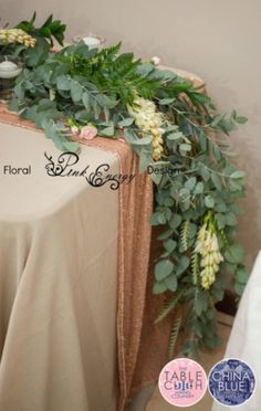 Greenery and flower table runner cascading down the sides. Linen from The Table Cloth Hiring Company.