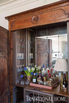 An antique armoire—from the apartment's previous incarnation—was  transformed into a luxuriously detailed (and easily hidden) bar. - Photo: Sara Essex Bradley / Design: Chad and Christina Graci