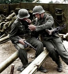 """Two German soldiers of the Grossdeutschland Division take a smoking break during the fight near Wikowischken in Lithuania, august 1944.note the captured russian cannons in the back."" - pin by Paolo Marzioli"
