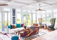 Oceanfront living room with colorful sofa and peacock chairs
