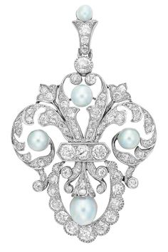 Platinum, Gold, Pearl and Diamond Pendant-Brooch, Marcus  Co.  The stylized fleur-de-lys mount enhanced by 4 pearls approximately 5.6 to 4.5 mm., set throughout with numerous old-mine cut diamonds, with pearl and diamond-set pendant loop, signed M  Co., circa 1905.
