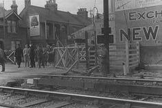 West Worthing level crossing (also known as Tarring level crossing) with damaged gates on the north side following an accident. A policeman wearing white gloves can be seen standing on the road together with curious onlookers.