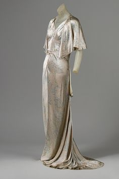 full-length sheaths  dominated the early 1930s, and short flapper dresses became a thing of the past. The small cape allowed for wear between 6-8, but the dress was designed for evening wear in Paris where the cocktail party was popular.