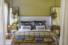 La suite principal de esta casa en un country tiene cama con cabecera revestida, lámparas colgantes, mesas de luz de madera, espejos con marco de hierro negro y alfombras a rayas.