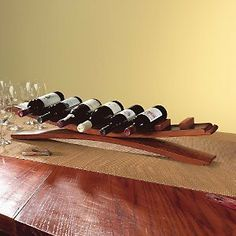 Arched Oak Stave Wine Rack by Wine Enthusiast. $69.95. Oak wine barrel staves are artfully arranged to let you display 7 of your best wine bottles. In the dining room before a sumptuous meal or in the wine cellar strategically placed this handsomely finished wood wine rack is eye-catching and inventive. Size: 6'H x 37'W x 5'W. Holds up to 7 wine bottles.
