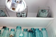 Bathroom storage and decor. Old blue glass jars and wire bins.