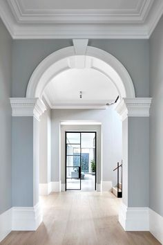 In the entryway, the architect seamlessly combined the existing heritage features with an expansive new extension. For example, the hallway, features a Victorian arch leading toward a glass steel door that opens onto the home's new addition Modern Victorian Homes, Victorian House Interiors, Victorian Interior Doors, Victorian Home Decor, Victorian Houses, Victorian Hallway, Victorian Living Room, Hallway Designs, Home Renovation