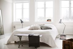 Modern minimalist scatter cushion arrangement on white bed. Image from decordots.com