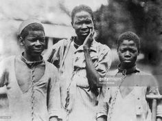 Three Abyssinian slaves in iron collars and chains.
