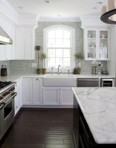 Gorgeous kitchen with light green/blue subway tiles, dark wood flooring, marble island counter tops, white, glass, and dark wood cabinets
