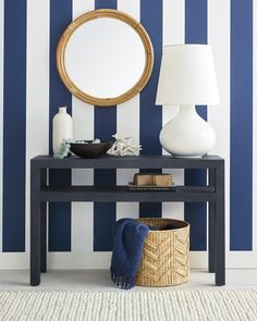 This coastal-inspired space is simply capturing. We love the raffia-wrapped console, rattan mirror, white lamp, and woven storage basket. Blue and white striped wallpaper sets a perfectly beachy scene here. Living Room Console, Decor, Striped Wallpaper, Elegant Homes, White Decor, Coastal Style Decorating, Coastal Decor, Table Design, Home Decor