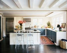 What a beautiful kitchen! Clean lines with no upper cabinets.  Notice how the rug is the only color in the room.  This rug is an antique Heriz.