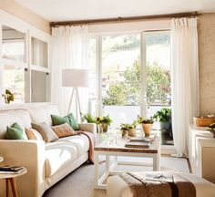 Sencilla y acogedora la decoración de este salón, toda en blanco y beige. Me gustan las cortinas* y los rieles* así, desde el techo.