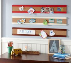 Buy this at PBK for $30 for 3 feet in two colors, OR make it yourself and personalize the trim to any color that matches your room using cork tiles and some trim, maybe some grosgrain ribbon?  Super cute way to display art in the kitchen (and not on your frig) , over a kid's desk like in the pic, or hung vertically on a narrow strip of wall to attach all those Save the Date cards/birthday invitations, or some favorite photos.