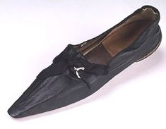 These fine black leather men's shoes show the further progression of latcheted shoes, here turned into very elegant dress slippers for dinner or dancing. Dated 1810-29, they foreshadow the long lines and square toes that shoes would achieve in the 1830s. This pair ties with silk ribbons, but I have seen examples that fasten with simpler cord.