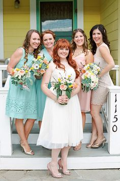 The gorgeous bride and her colorful bridesmaids pose for a photo opp with fresh bouquets.