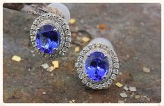 Estate oval tanzanite earrings:  Devastating violet-blue tanzanites sparkle their hearts out in these estate earrings.  10 x 8mm oval tanzanites are secured in 14K white gold four-prong settings, each with a double halo of diamonds.  These earrings are estate pieces and so, not unusually, they are clip-ons.  Talk to us about converting these beauties into posts.