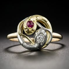 Antique Tri-Color Ruby and Diamond Snake Ring. Here is the only snake ring we've seen of this particular design. A mirror-image pair of of sinuous serpents, one diamond headed in platinum and the other ruby headed in 18K yellow gold, entwine to create a stylized yin-yang design. And just for another dash of contrast, the ring shank is 18K rosy-yellow gold. Circa 1900-1915.