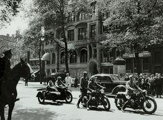 Afwachtend, maar misschien ook wel gelaten, staan omstanders te kijken hoe de Duitsers Amsterdam binnentrekken.