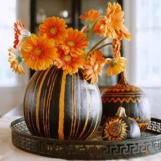 Black-and-Orange Pumpkin Display  A stunning centerpiece with pumpkins and fresh flowers.   Carve out a large pumpkin to hold a vase. Spray-paint your pumpkins with a black matte-finish paint. Once dry, scrape away the painted surface in lines or in the form of a sunflower or another design.