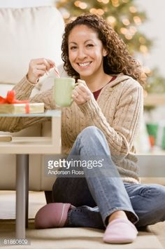 Stock-Foto : Hispanic woman stirring tea with candy cane