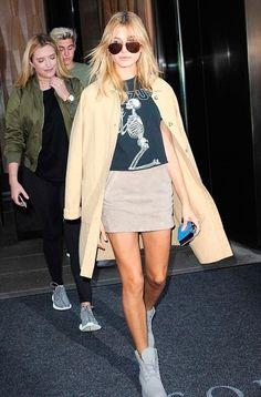 Hailey Baldwin usa mini saia descontraída com casaco sobretudo, t-shirt de banda e botas cinza