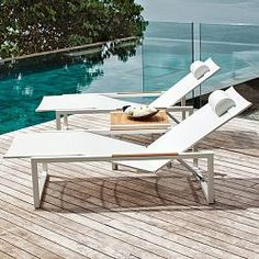 This contemporary designed outdoor chaise has a multi-position pneumatic back and a stainless steel frame with a white finish and teak inlaid arms. The chaise bed is made of Batyline fabric and includes a head rest. Batyline is a woven polyester mesh that is resistant to stretching, cracking and fading, very quick drying and resistant to staining. A matching side table with a slatted teak top is also available. Furniture frames have a 10 year warranty against manufacturing workmanship and…