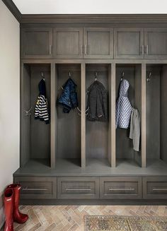 Red brick herringbone pavers accent brown oak drawers donning satin nickel pulls and positioned beneath gray oak open lockers fitted with polished nickel hooks mounted beneath gray oak shaker cabinets.