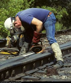 RailPictures.Net Photo: A little human interest: In 1990, a CSX welder grinds down his weld on the frog at the turnout at the south end of Starnes (VA) siding. Track work like this takes a pounding, so it's a constant effort to keep it up to spec. I regret I didn't get this guy's name. Notice the flame-resistant material wrapped around the bottom of his pants. Without those, his blue jeans would like catch fire from the sparks! by Ron Flanary