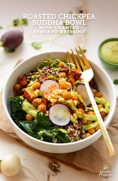 A clean, organic Buddha bowl, packed with roasted chickpeas, butternut squash, kale, quinoa, garlic and spices, then topped with a drizzle of fresh cilantro avocado dressing.