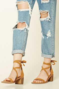 A pair of faux suede heels featuring a self-tie ankle strap, open toe, and a wooden-look block heel.