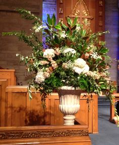 altar urns of white hydrangeas, queen anne's lace, peach stock, light pink guara, seeded eucalyptus, magnolia, olive branches, & maiden hair fern