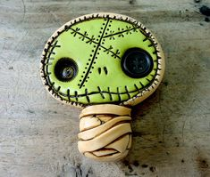 Zombie mummy brooch in light peach with green face. A cute dead face full of scars. He has a black button eye