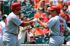 BALTIMORE, MD - AUGUST 10: Jon Jay #19 (L) congratulates Kolten Wong #16 of the St. Louis Cardinals after scoring against the Baltimore Orio...